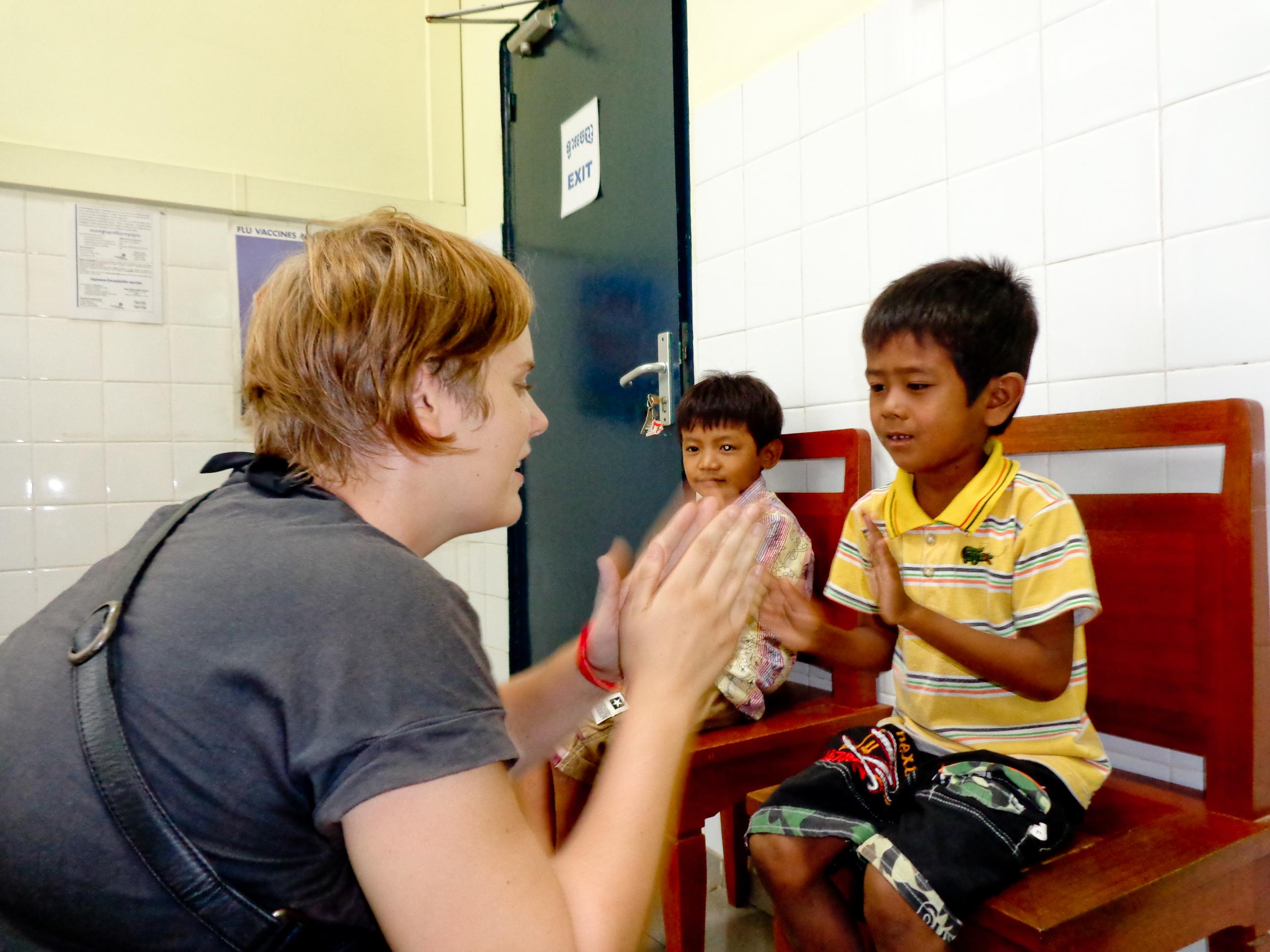 A female intern from projects Abroad can be seen clapping with a child during her occupational therapy internship in Cambodia.